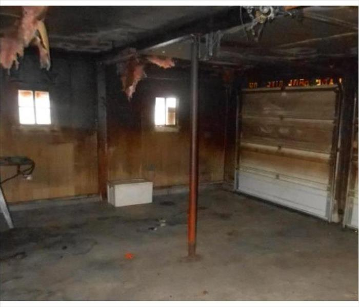 garage blackened by fire, hanging insulation damage door