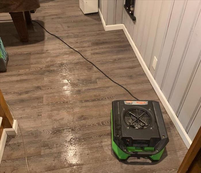 air mover drying out wet hardwood floor in gameroom