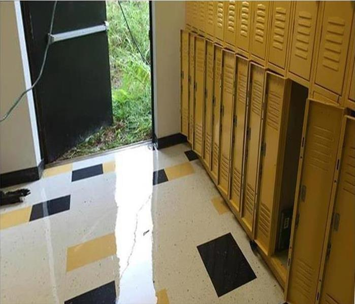 water puddling on tile floor, lockers, open exit door