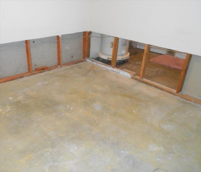 the visible concrete floor pad, water heater, and cut and removed lower wall sections