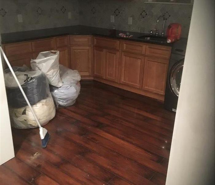 debris in bags, broom, wet still wood floor in a kitchen
