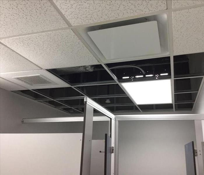 The drop ceiling is cleared of damaged tiles, shows inset lighting