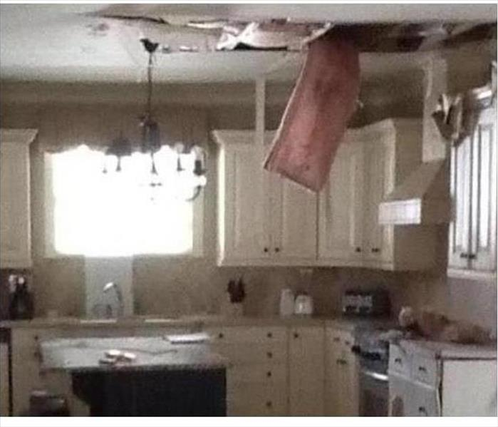 hanging insulation from a damaged ceiling in a kitchen