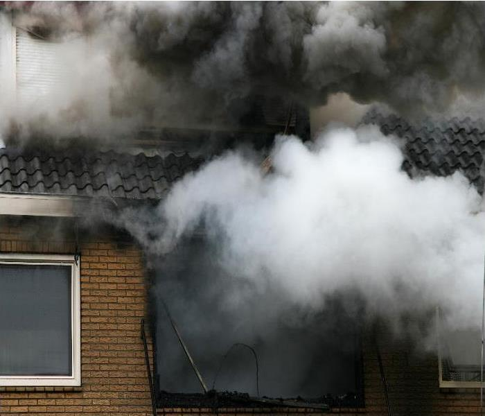 Big fumes of smoke coming out of the second floor of a home