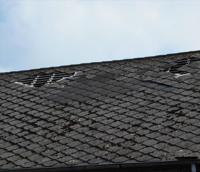 shingles missing off the roof of a house.